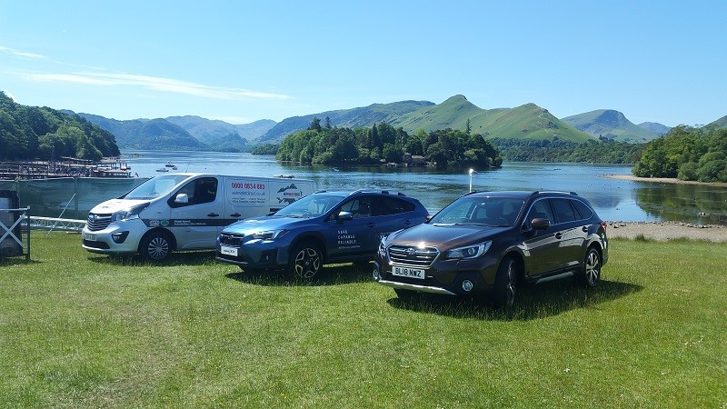 a van and two cars in front of a lake on a sunny day