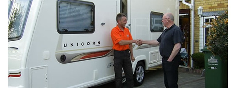 two men shaking hands in front of a caravan