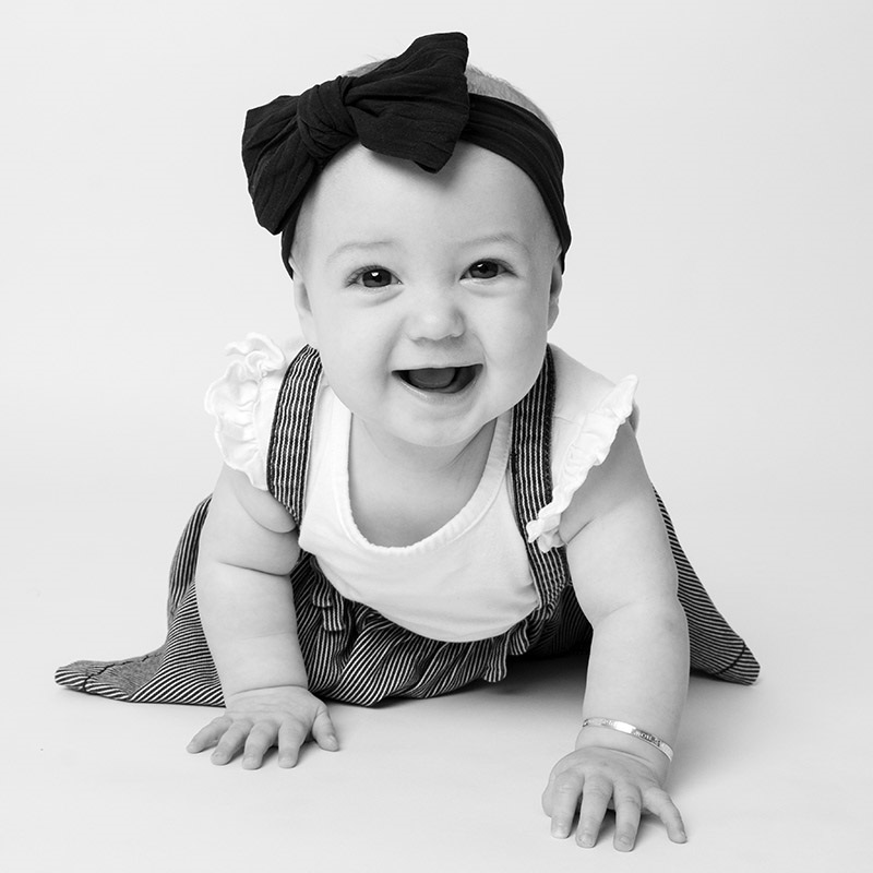 baby crawling wearing a bow on its head