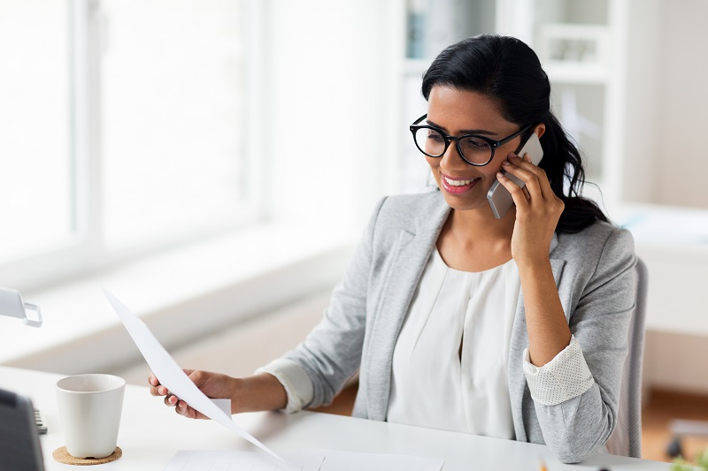brokerplan female franchisee with glasses on the phone holding a piece of paper