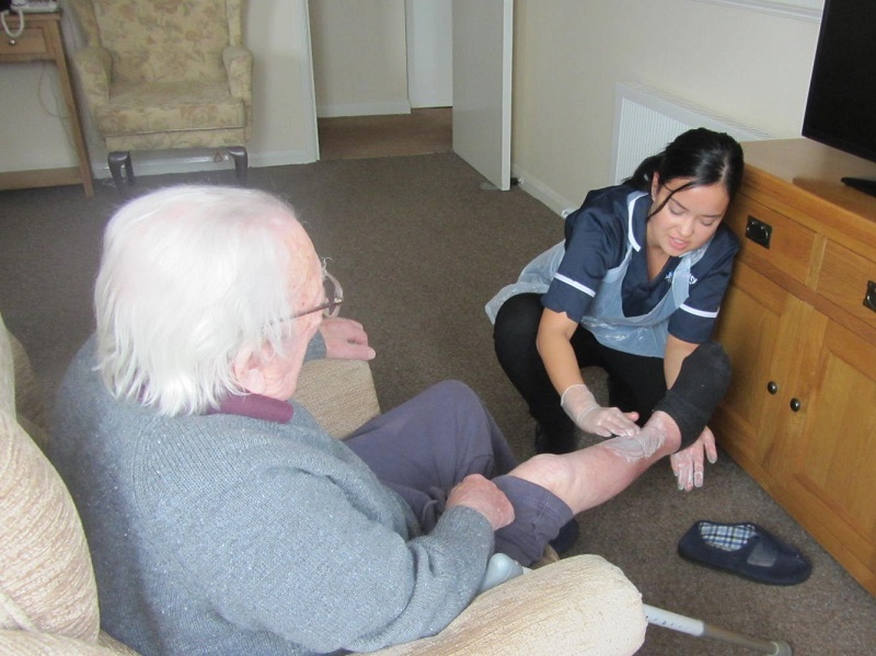 Carer applying cream to elderly mans leg