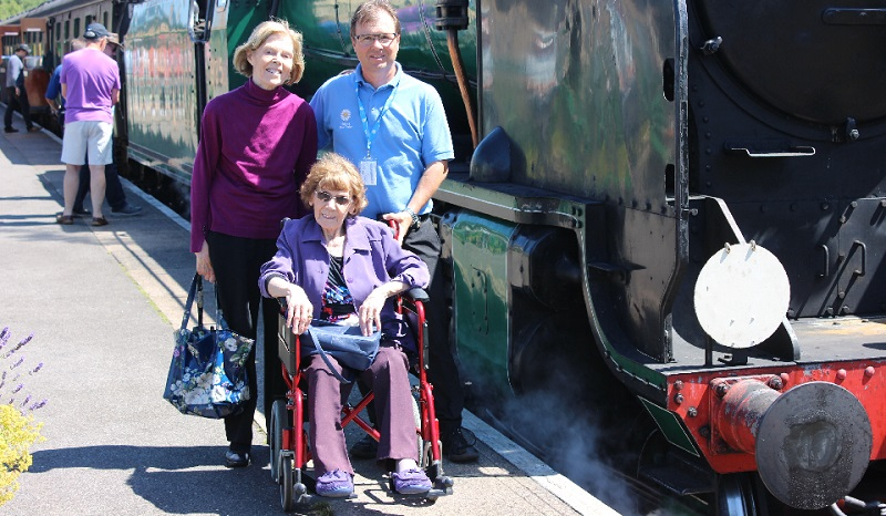 Driving Miss Daisy franchisee with customers next to steam train