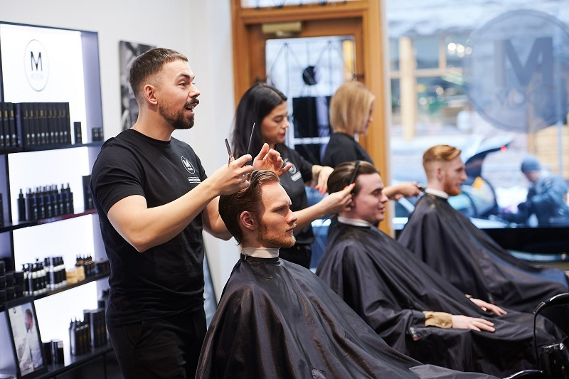 MRoom barbers cutting customers hair inside salon