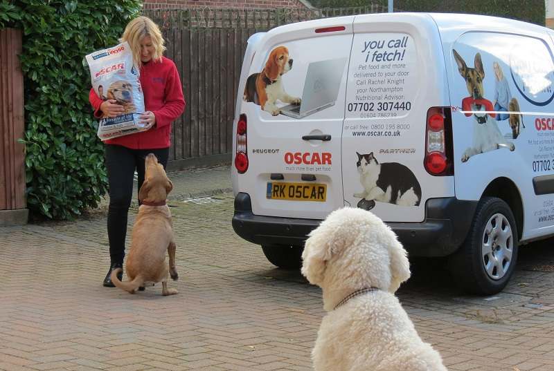oscar pet foods franchisee greeting a dog