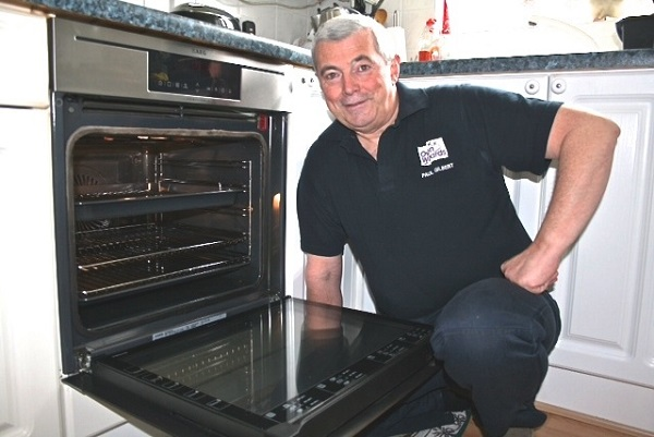 Oven Wizards franchisee Paul Gilbert in front of a clean oven