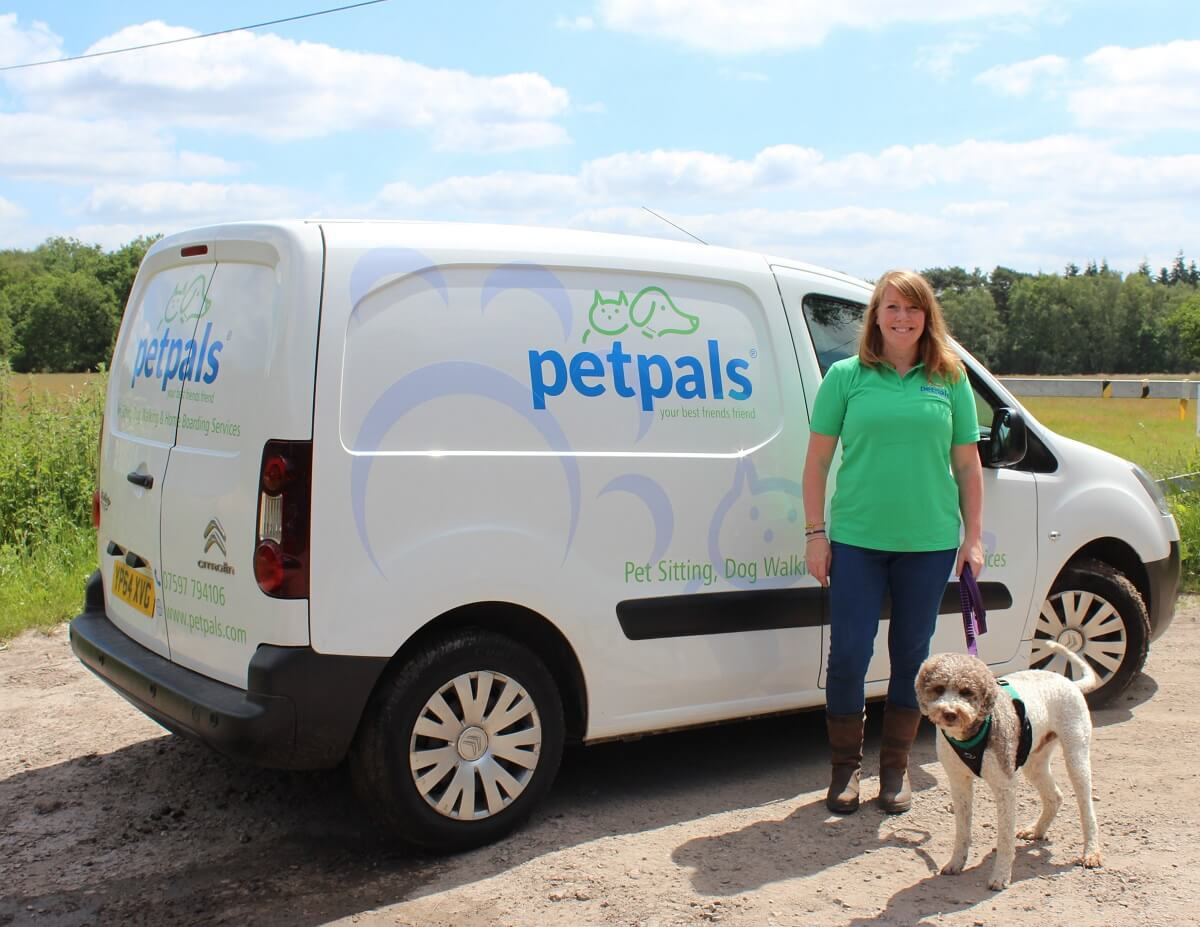 Petpals franchisee with her dog beside a van