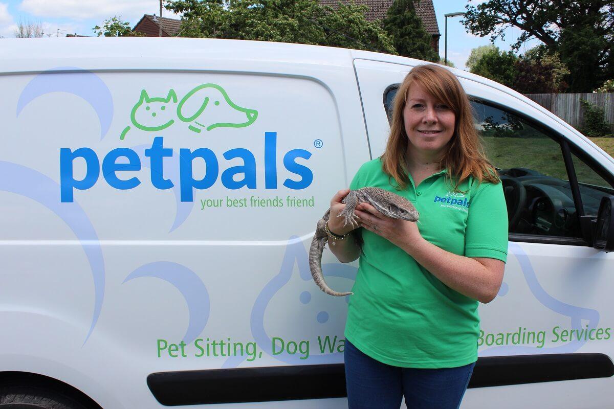Petpals franchise holding a lizard beside a van