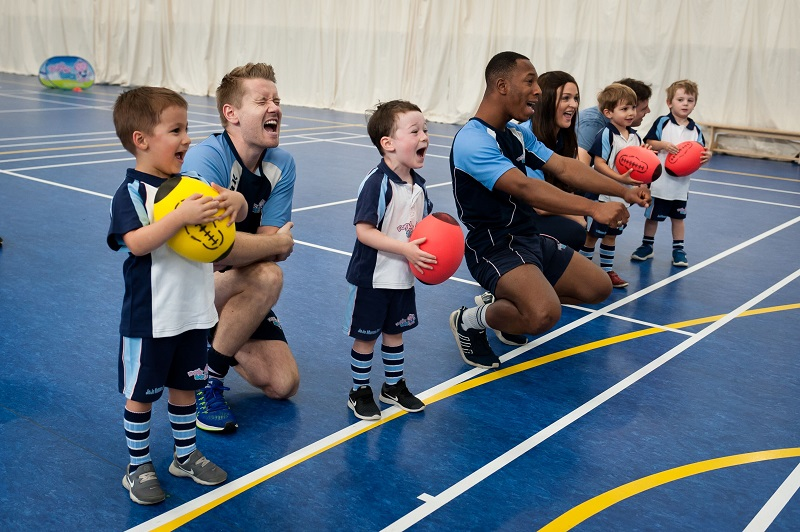 Kids learning to play rugby with two Rugbytots coaches