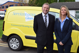 Servicemaster franchisees team of husband and wife next to their van