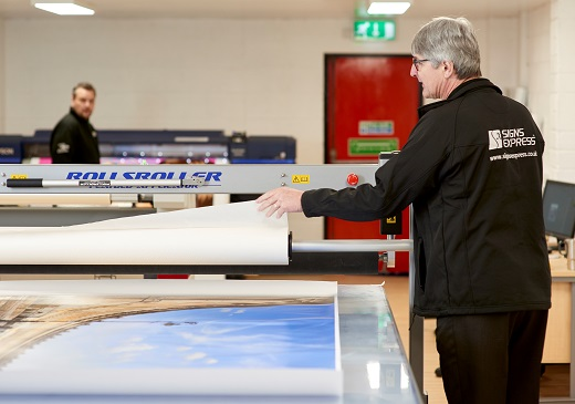 Signs Express employee using a printer