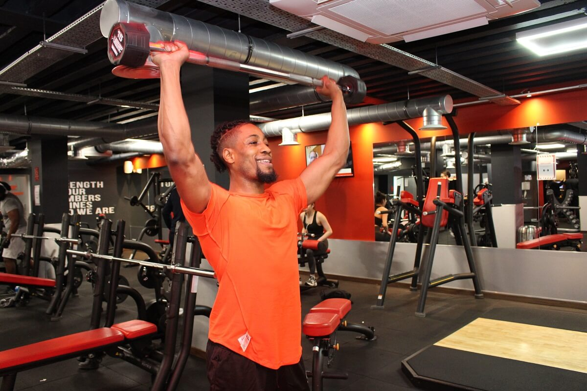 snap fitness gym goer lifting weights
