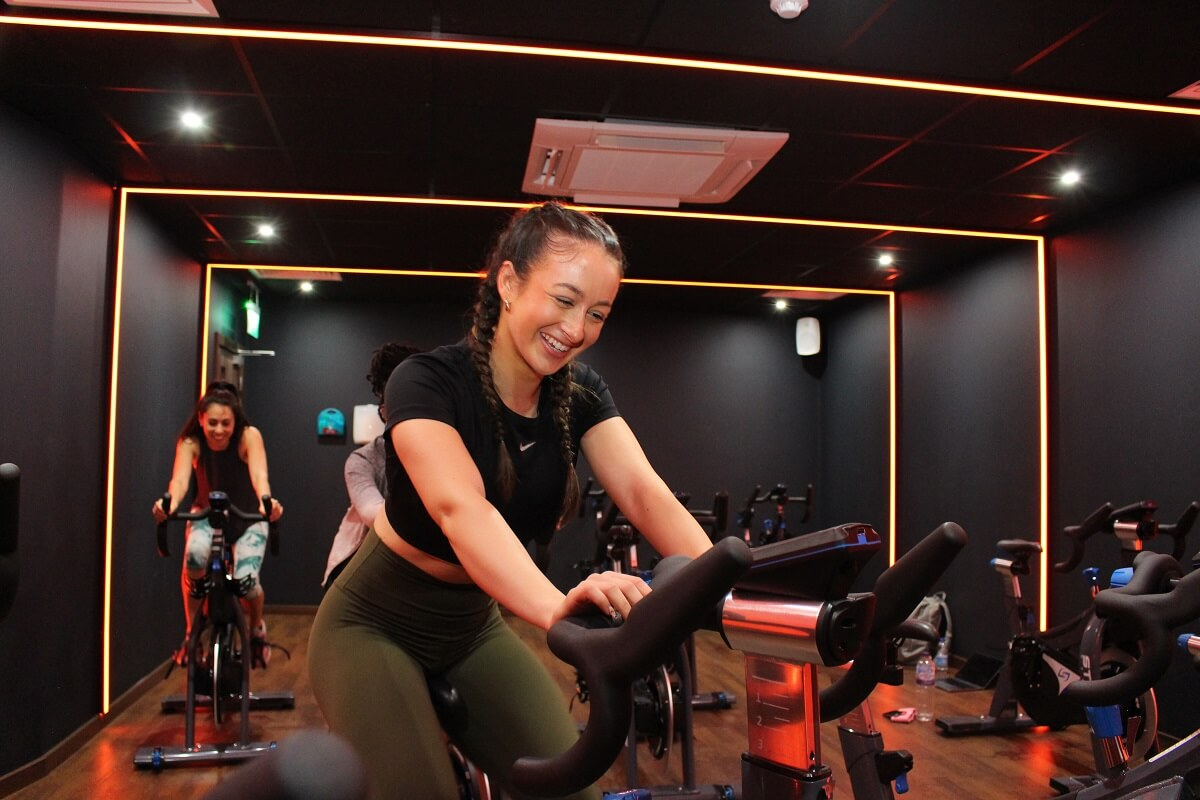 snap fitness gym goer working out on an exercise bike