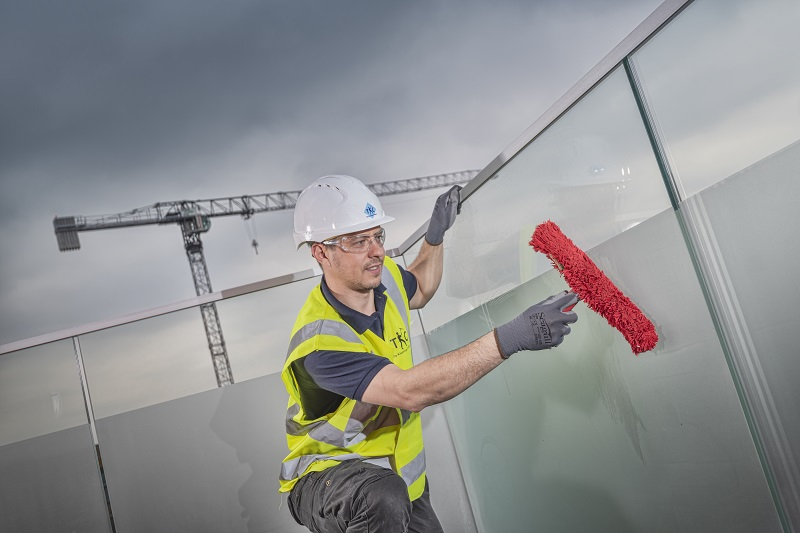 The Kleaning Company worker cleaning a high rise window