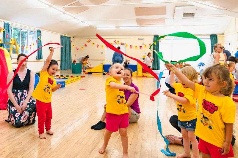 children playing with ribbons in a Tumble Tots class