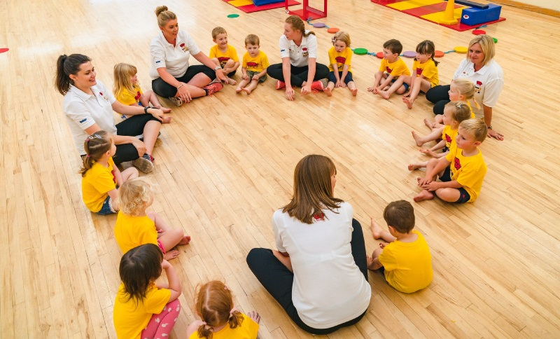 Children sitting in a circle in their Tumble Tots class