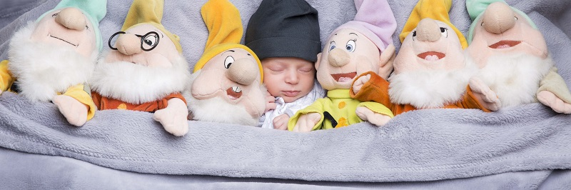 baby in bed between toy seven dwarves by venture photography