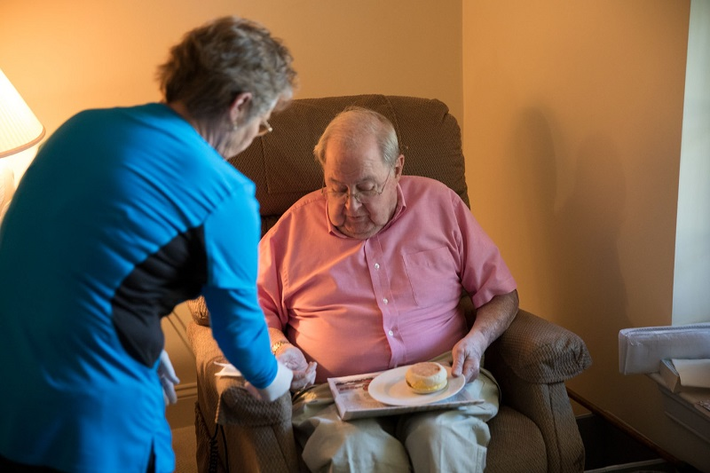 FirstLight carer giving client their dinner